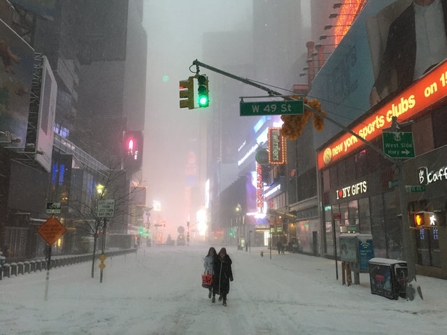 """Times Square under the grip of Storm Jonas. During the storm, all travel systems were suspended, leaving the iconic square to the intrepid pedestrians"". (Photo by Phil Darling/The Guardian)"
