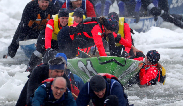 A member of Team Chez Victor falls in the water while competing during the Ice Canoe race at the Quebec Winter Carnival in Quebec City, February 5, 2017