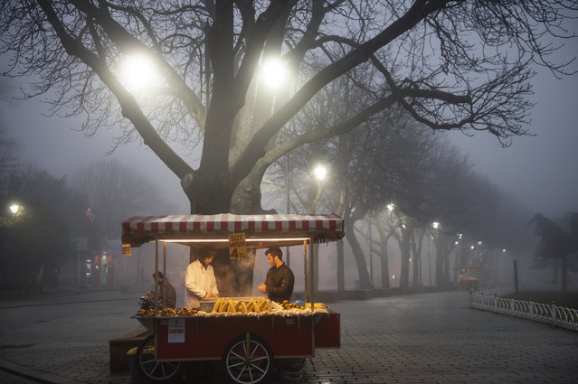 Street vendors sell corn on Sultanahmet Square near the Blue mosque on a foggy day in Istanbul, on February 20, 2019. (Photo by Yasin Akgul/AFP Photo)