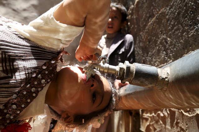A girl drinks water from a faucet amid an acute shortage of clean drinking water in Sanaa, April 24, 2015. (Photo by Mohamed al-Sayaghi/Reuters)