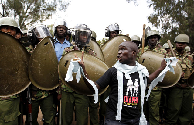 "A protester mocks riot police as he chants slogans during a march dubbed ""Kenya ni Kwetu"" in Kenya's capital Nairobi February 13, 2014. Kenyan police in riot gear fired teargas to disperse more than 200 protesters marching towards the parliament to demonstrate against corruption, insecurity, unemployment, poverty, according to the organisers. ""Kenya ni Kwetu"" in Swahili means, ""Kenya is home"". (Photo by Thomas Mukoya/Reuters)"