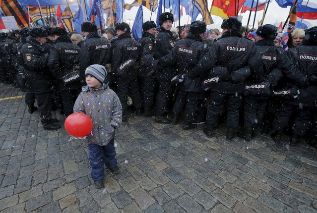 A boy stands in front of Russian police officers during a festive concert marking the second anniversary of Russia's annexation of the Crimea region, in Red Square in central Moscow, Russia, March 18, 2016. (Photo by Maxim Shemetov/Reuters)