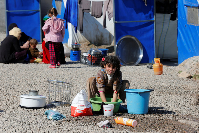 A displaced Iraqi child who fled the Islamic State stronghold of Mosul with her family, looks to the camera as she washes dishes at Khazer camp, Iraq, February 8, 2017. (Photo by Muhammad Hamed/Reuters)