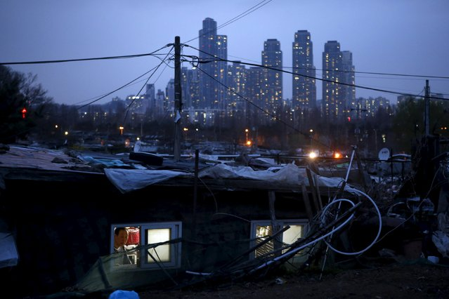 A man looks out from his shack as a luxury high-rise apartment complex is seen in the background at Guryong village in Seoul, South Korea, April 2, 2015. Demolition of Guryong, the last slum in Seoul's glitzy Gangnam district, is expected to start this summer after redevelopment plans were mired for years in squabbling among the city, district and developers, and even battling residents. (Photo by Kim Hong-Ji/Reuters)