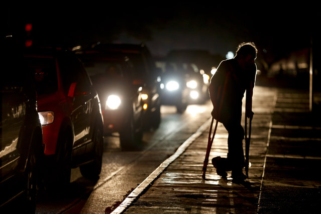 In this March 29, 2019 file photo, a man on crutches is illuminated by headlights of oncoming traffic, in Caracas, Venezuela. Venezuelans are struggling to understand the Sunday, March 31, 2019 announcement that the nation's electricity is being rationed to combat daily blackouts. (Photo by Natacha Pisarenko/AP Photo)