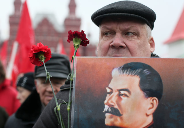 A man holds a portrait of Josef Stalin before laying flowers at the grave of the late Soviet leader during a ceremony to mark the 61th anniversary of Stalin's death in the Red Square in Moscow, Russia, March 5, 2014. Josef Stalin died on March 5,1953 at the age of 74. (Photo by Sergei Ilnitsky/EPA)