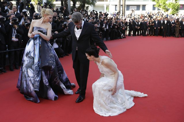 "Cate Blanchett and director Todd Haynes turn to help Rooney Mara as she adjusts her dress upon arrival for the screening of the film ""Carol"" at the 68th international film festival, Cannes, southern France, Sunday, May 17, 2015. (Photo by Lionel Cironneau/AP Photo)"