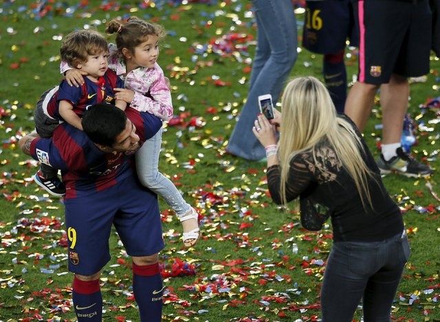 Barcelona's Luis Suarez (L) holds his children Delfina and Benjamin (L, top) while his wife Sofia Balbi takes a picture during celebrations for winning the Spanish first division soccer league at Camp Nou stadium in Barcelona, Spain, May 23, 2015. (Photo by Albert Gea/Reuters)