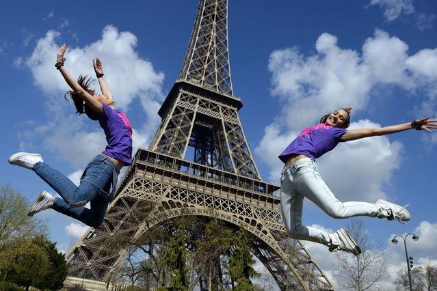 Two Bulgarian tourists pose in front of the Eiffel Tower in Paris on their last day in the capital on March 24, 2014. (Photo by Franck Fife/AFP Photo)
