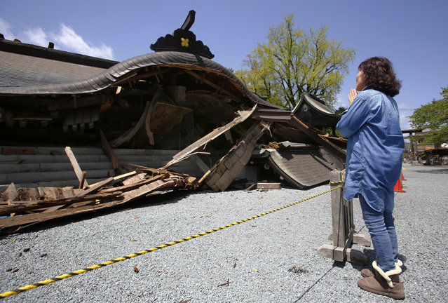 A woman prays in front of the historic Aso Shrine collapsed by powerful earthquakes in Aso, Kumamoto prefecture,  Japan, Sunday, April 17, 2016. Two nights of increasingly terrifying earthquakes flattened houses and triggered major landslides. (Photo by Shizuo Kambayashi/AP Photo)