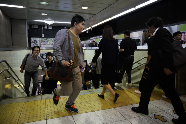 In this Friday, May 24, 2019, photo, two commuters run up the steps to catch a Yamanote Line train at Shinjuku Station in Tokyo. Want to take a glimpse of daily life in downtown Tokyo? Take a ride on the Yamanote loop line. For most Tokyoites, the line means an incredibly punctual and efficient transportation system for commuting. For tourists, it offers a glimpse into the life of ordinary people living in the city. (Photo by Jae C. Hong/AP Photo)