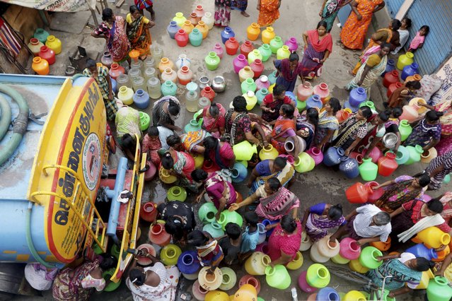 Indiand stand in queues to fill vessels filled with drinking water from a water tanker in Chennai, capital of the southern Indian state of Tamil Nadu, Wednesday, June 19, 2019. Millions of people are turning to water tank trucks in the state as house and hotel taps run dry in an acute water shortage caused by drying lakes and depleted groundwater. Some private companies have asked employees to work from home and several restaurants are closing early and even considering stopping lunch meals if the water scarcity aggravates. (Photo by R. Parthibhan/AP Photo)