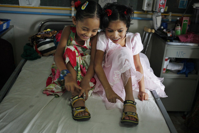 In this July 15, 2015 photo, Nepalese amputee victims Khendo Tamang, left, and Nirmala Pariyar, both 8, share a single pair of shoes at the Bir Trauma Center in Kathmandu, Nepal. After suffering serious leg wounds in Nepal's massive 2015 earthquake that killed and injured thousands, both girls were brought to the Bir Trauma Center in Kathmandu, to receive single leg amputations. Following their surgeries, Nirmala's relentless cheerfulness drew a still very depressed Khendo close and both found an inseparable friendship which has helped their emotional wounds heal. (Photo by Niranjan Shrestha/AP Photo)