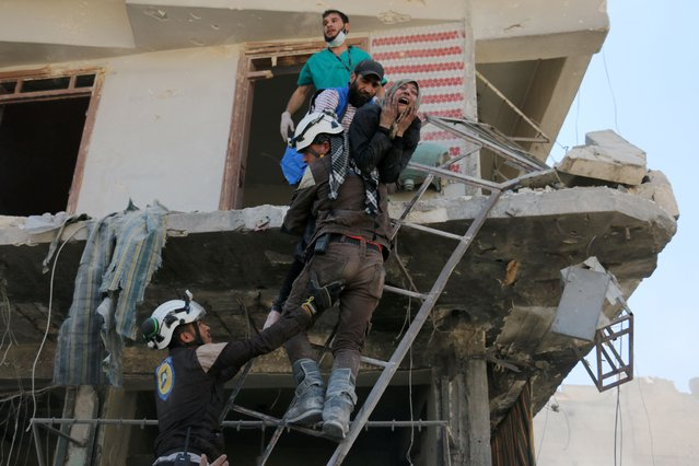 Syrian civil defence volunteers evacuate people from a damaged building following a reported airstrike on April 23, 2016 in the rebel-held neighbourhood of Tareeq al-Bab in the northern city of Aleppo. The barrage of air strikes on Aleppo began around 10:00 local time and hit several neighbourhoods, including the heavily-populated Bustan al-Qasr district, an AFP correspondent in the city said. But the deadliest raid was on the Tareeq al-Bab neighbourhood on the eastern edges of the city. (Photo by Ameer Alhalbi/AFP Photo)