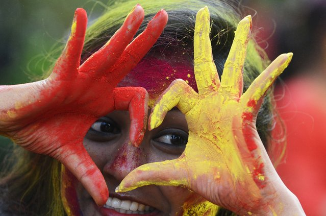 "Indian students play with coloured powders as they celebrate ""holi"" or the ""festival of colours"" during a special function in Kolkata on March 12, 2017. (Photo by Dibyangshu Sarkar/AFP Photo)"
