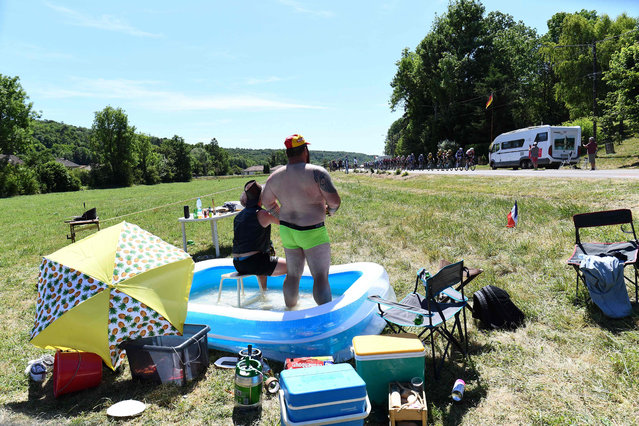 In this file photo taken on July 09, 2019 Spectators refresh themselves in a swimming pool as they watch cyclists riding during the fourth stage of the 106th edition of the Tour de France cycling race between Reims and Nancy, eastern France. (Photo by Anne-Christine Poujoulat/AFP Photo)