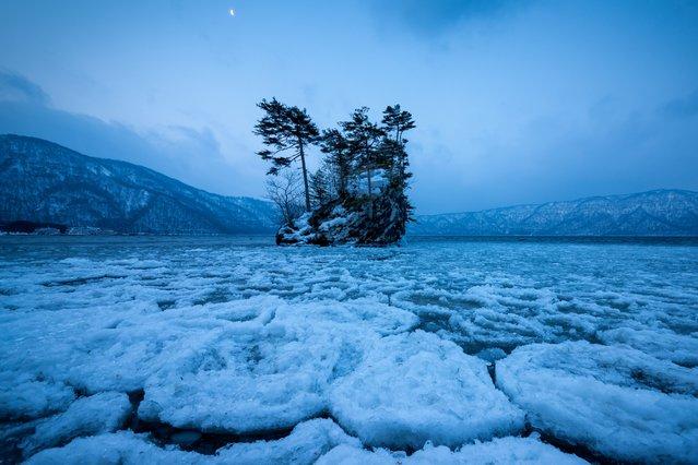 """Frozen lake"". Lake had frozen the morning waning moon is visible. Photo location: Lake Towada Aomori, Japan. (Photo and caption by Sho Shibata/National Geographic Photo Contest)"