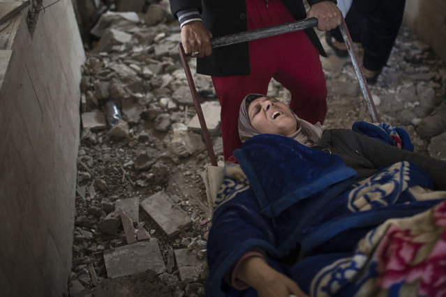 An injured woman is carried on a cart through a destroyed train station during fighting between Iraqi security forces and Islamic State militants, on the western side of Mosul, Iraq, Sunday, March 19, 2017. More than 750 civilians have been killed or wounded in the first month of fighting in the Iraqi offensive to retake western Mosul from the Islamic State group, front-line medics say. Iraqi forces have increasingly turned to airstrikes and artillery in the heavily populated urban terrain, and impoverished residents running out of food are forced to flee their homes, making dangerous journeys across front lines. (Photo by Felipe Dana/AP Photo)