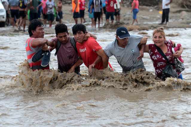 Residents cross the Viru river after Viru bridge at the Pan American highway collapsed after a massive landslide and flood in Trujillo, northern Peru, March 20, 2017. (Photo by Douglas Juarez/Reuters)