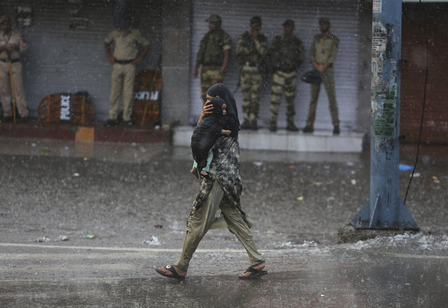 A woman carries her child as she walks past Indian security personnel as it rains during curfew like restrictions in Jammu, India, Monday, August 5, 2019. An indefinite security lockdown was in place in the Indian-controlled portion of divided Kashmir on Monday, stranding millions in their homes as authorities also suspended some internet services and deployed thousands of fresh troops around the increasingly tense region. (Photo by Channi Anand/AP Photo)