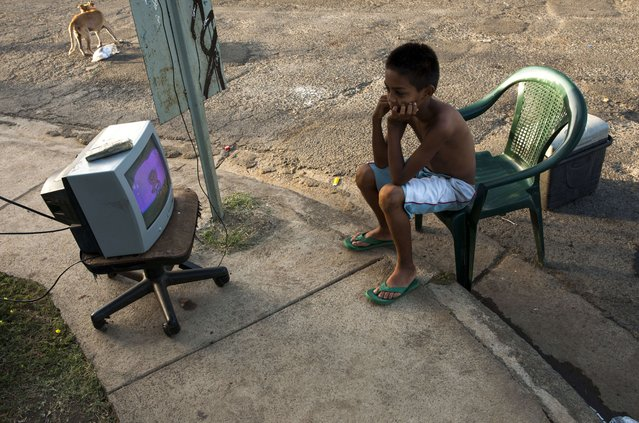 A boy watches TV on a street in Managua on April 14, 2014, as tremors have not stopped in Nicaragua since April 10 when a 6.2-magnitude earthquake hit the country's Pacific region. The quakes that struck Nicaragua in the past days killed one person, left 40 injured and damaged more than two thousand homes, according to official sources. (Photo by Inti Ocon/AFP Photo)