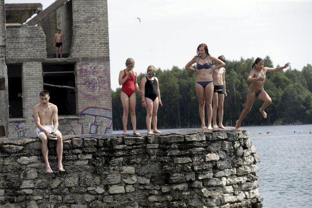 People jump into the water near Murru prison, an abandoned Soviet prison, in Rummu quarry, Estonia, during hot weather July 4, 2015. (Photo by Ints Kalnins/Reuters)