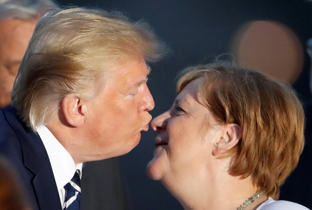 President Donald Trump and German Chancellor Angela Merkel lean in for a kiss during the family photo with invited guests at the G7 summit in Biarritz, France August 25, 2019. (Photo by Christian Hartmann/Reuters)