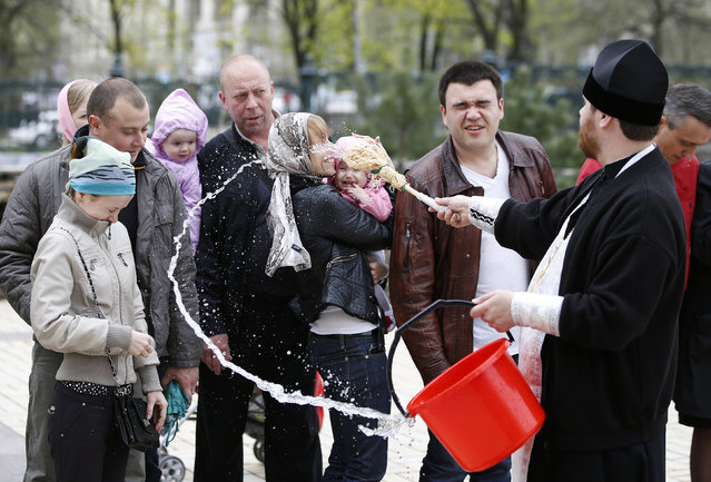 A Ukrainian Orthodox priest sprinkles holy water on believers during Easter in Donetsk, eastern Ukraine April 20, 2014. (Photo by Marko Djurica/Reuters)