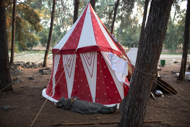 In this Friday, July 3, 2015 photo, an Israeli member of a knight club wearing a medieval costume rests in their camp before the reenactment of the Battle of Hattin in Lavi Forest, northern Israel. (Photo by Oded Balilty/AP Photo)