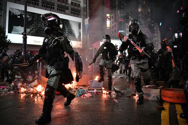 Police run past debris set alight by protesters in the Causeway Bay area of Hong Kong on August 31, 2019, as people demonstrate, defying a ban on rallying – and mounting threats from China – to take to the streets for a 13th straight weekend. (Photo by Anthony Wallace/AFP Photo)