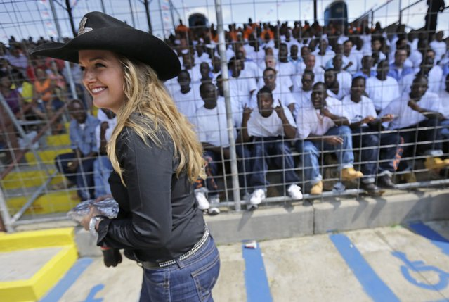 Miss Rodeo Louisiana Hannah Bergeron walks past the inmate section at the Angola Prison Rodeo in Angola, La., Saturday, April 26, 2014. In a half-century, the event has grown from a small event for prisoners into a big business that draws thousands of spectators to the Louisiana State Penitentiary. (Photo by Gerald Herbert/AP Photo)