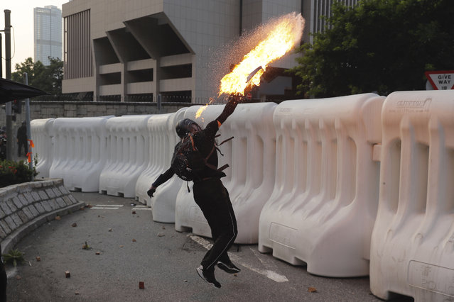 An anti-government protester throws a Molotov cocktail during a demonstration near Central Government Complex in Hong Kong, Sunday, September 15, 2019. (Photo by Kin Cheung/AP Photo)