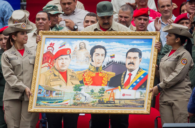 Venezuelan President, Nicolas Maduro (C) holds a painting depicting (L-R) late Venezuelan President Hugo Chavez, Venezuelan liberator Simon Bolivar and current President Maduro, as he attends a march of members of the Venezuelan National Bolivarian Militia to commemorate their seventh anniversary in Caracas, Venezuela, 17 April 2017. (Photo by Miguel Gutierrez/EPA)
