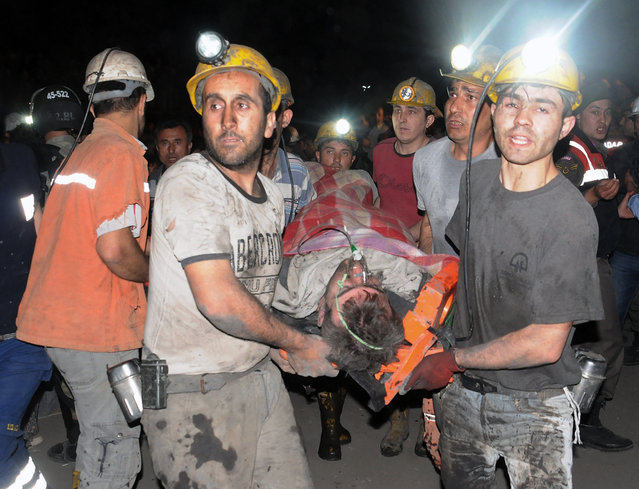 Miners carry a rescued miner after an explosion and fire at a coal mine killed at least 17 miners and left up to 300 workers trapped underground, in Soma, in western Turkey, Tuesday, May 13, 2014, a Turkish official said. Twenty people were rescued from the mine but one later died in the hospital, Soma administrator Mehmet Bahattin Atci told reporters. The town is 250 kilometers (155 miles) south of Istanbul. The death toll was expected to rise. (Photo by AP Photo/Depo Photos)
