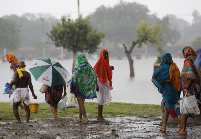 Hindu devotees return home in the rain after offering rituals in the River Ganges in Prayagraj, in the northern Indian state of Uttar Pradesh, Saturday, September 28, 2019. A heavy spell of retreating monsoon rains has flooded wide areas in northern India, killing dozens of people this week, an official said Saturday. Sandhaya Kureel, a spokeswoman of the Disaster Management and Relief Department, said most of the 59 fatalities were caused by house collapses, lightning and drowning in Uttar Pradesh state. (Photo by Rajesh Kumar Singh/AP Photo)