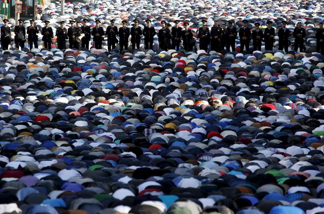 Interior Ministry members stand guard as Muslims attend the morning prayers of Eid al-Fitr holiday, marking the end of the holy month of Ramadan, in Moscow, Russia, July 17, 2015. (Photo by Sergei Karpukhin/Reuters)