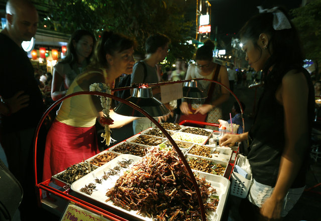 Foreign tourists buy fried insects from a Thai vendor at Khao Sarn road, a spot tourist area in Bangkok, Thailand, 20 July 2013. Insects have long been on the menu in Thailand, but academics and the United Nation's Food and Agriculture Organization (FAO) officials are hoping they will become a more common global source of protein and nutrients to meet the need for growing world food requirements in the future. (Photo by Narong Sangnak/EPA)