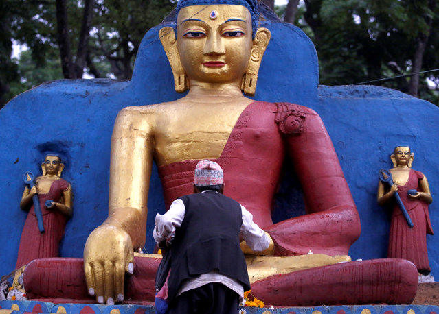 A devotee offers prayer on the idol of Buddha during the birth anniversary of Buddha, also known as Vesak Day, at Swayambhu in Kathmandu, Nepal on May 10, 2017. (Photo by Navesh Chitrakar/Reuters)
