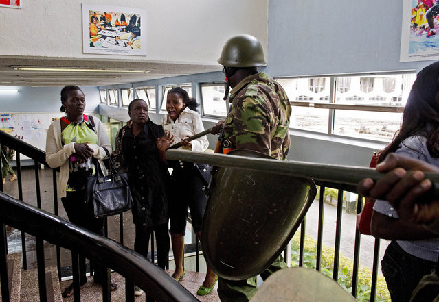 Kenyan riot police question students inside Nairobi University on May 20, 2014. The students were demonstrating against a controversial fee increment which ended in a riot with tear gas fired and riot police forcing their way inside the university to arrest students after rocks were thrown. (Photo by Carl de Souza/AFP Photo)