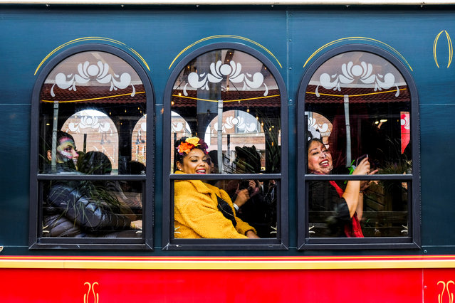 Women sit on a trolley as the Mexican-American community of Pilsen celebrates Day of the Dead with multiple celebrations through their neighborhood in Chicago, Illinois, U.S. November 2, 2019. (Photo by Maria Alejandra Cardona/Reuters)