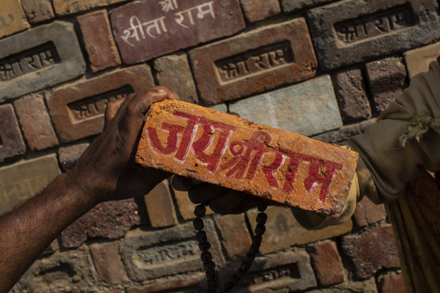 """In this Sunday, November 25, 2018 photo, a man holds a brick reading """"Jai Shree Ram"""" (Victory to Lord Ram) as bricks of the old Babri Mosque are piled up in Ayodhya, in the central Indian state of Uttar Pradesh. State-run broadcaster on Saturday, Nov. 9, 2019, said top court rules for disputed temple-mosque land for Hindus with alternate land to Muslims. Authorities increased security in Ayodhya, 550 kilometers (350 miles) east of New Delhi, and deployed more than 5,000 paramilitary forces to prevent any attacks by Hindu activists on Muslims, who comprise 6% of the town's more than 55,500 people. (Photo by Bernat Armangue/AP Photo/File)"""