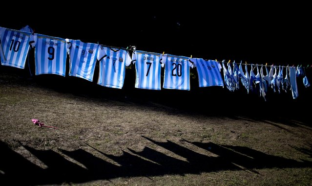 Argentina's national soccer team T-shirts hang for sale outside the Argentine Soccer Association in Buenos Aires before the team headed for Brazil, June 9, 2014. (Photo by Natacha Pisarenko/Associated Press)
