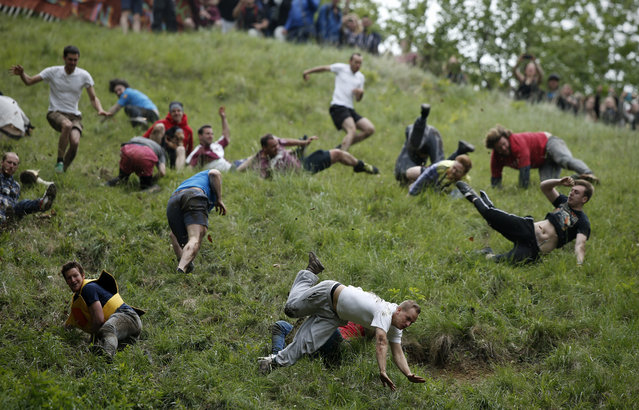Competitors tumble down Coopers Hill in pursuit of a round Double Gloucester cheese during an annual cheese rolling competition near the village of Brockworth, Gloucester, in western England, on May 30, 2016. The annual Cooper's Hill Cheese Rolling involves competitors chasing an eight pound Double Gloucester cheese down a steep hill. The slope has a gradient in places of 1-in-2 and in others 1-in-1, its surface is very rough and uneven and it is almost impossible to remain on foot for the descent. The winner of the downhill race wins the cheese. (Photo by Adrian Dennis/AFP Photo)