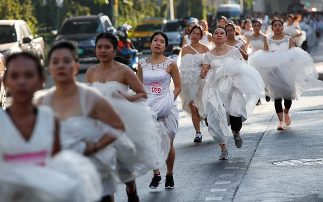 """Thai brides-to-be wearing bridal gowns compete in the """"Running of the Brides"""" event in Bangkok, Thailand, 24 November 2019. One hundred fifty couples of to be brides and their grooms compete in a three kilometers run race and challenge in seven tasks aimed to win a wedding package prizes including a pair of diamond rings and honeymoon trip to the Maldives. (Photo by Rungroj Yongrit/EPA/EFE/Rex Features/Shutterstock)"""