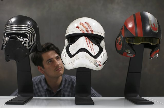 "A worker looks at replicas of Kylo Ren's helmet, Finn's Stormtrooper helmet and Poe Dameron's helmet from ""Star Wars: The Force Awakens"", in the Propshop headquarters at Pinewood Studios near London, Britain May 25, 2016. (Photo by Peter Nicholls/Reuters)"