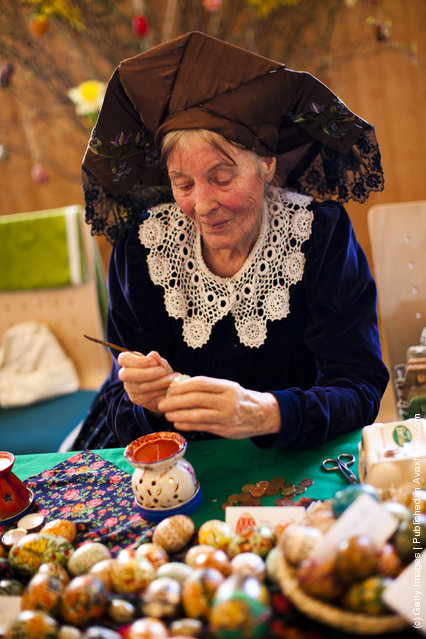 Sigrid Bolduan from the village Klein Loitz, wearing a traditional Lusatian sorbian folk dress, paints an Easter egg in traditional Sorbian motives at the annual Easter egg market