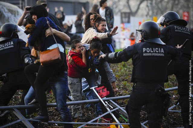 A child cries as riot police clash with demonstrators during a 24-hour strike on March 29, 2012 in Barcelona, Spain