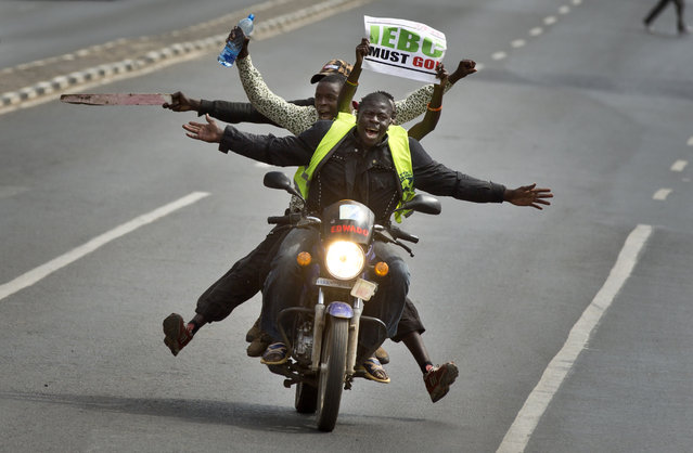 A motorcycle carrying protesters holding a placard using the acronym of the national electoral commission, drives ahead of demonstrators on foot calling for the disbandment of the commission over allegations of bias and corruption, in downtown Nairobi, Kenya Monday, June 6, 2016. (Photo by Ben Curtis/AP Photo)