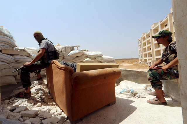 Nusra Front fighters rest with their weapons behind sandbags in the Sheikh Maksoud neighborhood of Aleppo, Syria August 3, 2015. (Photo by Abdalrhman Ismail/Reuters)