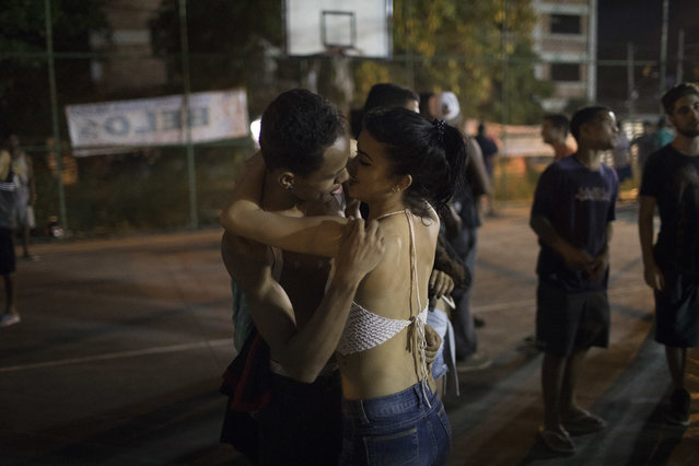 In this June 8, 2017 photo, a couple kiss on the sidelines of a night rap battle session in the City of God slum of Rio de Janeiro, Brazil. Freestyle rap battles are a way for some residents to express their frustration with the violence that permeates their daily lives in one of Rio's most notorious slums. (Photo by Leo Correa/AP Photo)